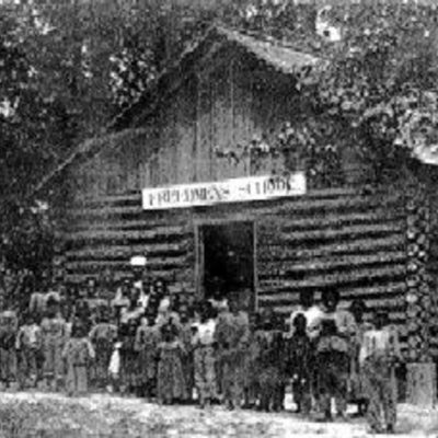 Members of the Freedmen's Colony stand in front of a log structure on Roanoke Island