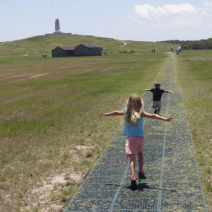 Two children, a girl and a boy, with their arms outstretched run along the path of the first flight at Wright Brothers National Memorial.