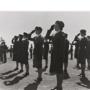 Group of Women Airforce Service Pilots (WASPs) saluting on field.