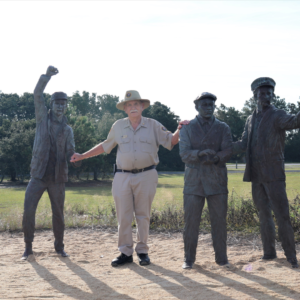 Volunteer Fred Hattman stands with Wright Brothers statues at Wright Brothers National Memorial on a sunny day