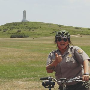 A female park ranger gives the thumbs up sign while sitting on a bicycle with Wright Brothers National Memorial in the background.