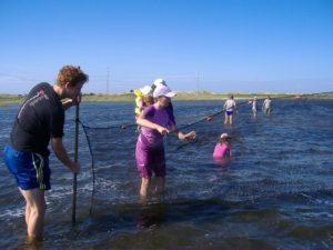 A group of men and women try castnetting on Cape Hatteras National Seashore.