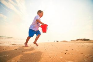 A young boy runs with a red bucket on Cape Hatteras National Seashore.