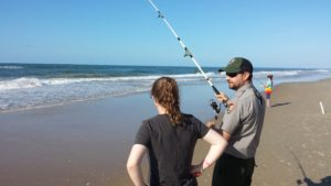 A male ranger holds a fishing pole while talking to a female visitor on the beach at Cape Hatteras National Seashore with the ocean in the background.