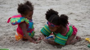 Two little girls play in the sand while wearing life jackets.