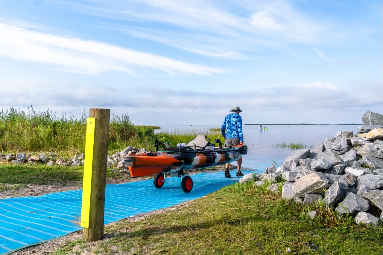 Trip Forman, President of Outer Banks Forever Board of Directors, pulls a red kayak toward the Pamlico Sound at the new kayak launch at Oregon Inlet Fishing Center.